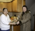 Meals on Wheels client Joan Atkinson (left) receives a delivery from volunteer Barbara Hartford
